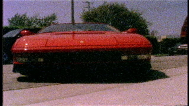 low angle red ferrari pulling into driveway in los angeles - grundstück stock-videos und b-roll-filmmaterial