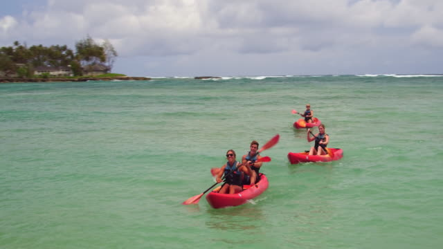low angle reverse tracking shot of four people kayaking in the ocean - turtle bay hawaii stock videos & royalty-free footage