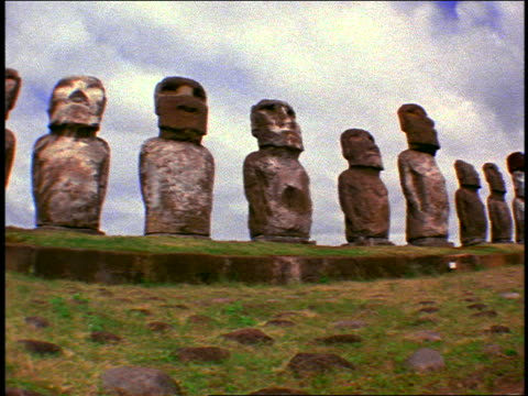 FISHEYE low angle PAN row of stone statues of varying heights on terraced field / Easter Island