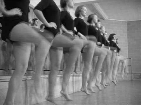 b/w 1953 low angle rows of young women in black leotards practicing dance kicks / documentary - showgirl stock videos and b-roll footage