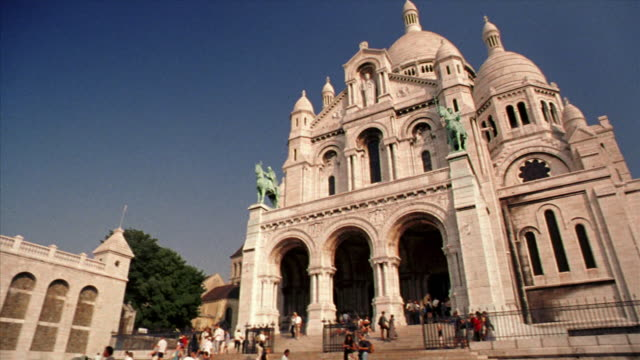 low angle pan sacre-coeur church with people on steps in montmarte / paris, france - basilique du sacre coeur montmartre stock videos & royalty-free footage