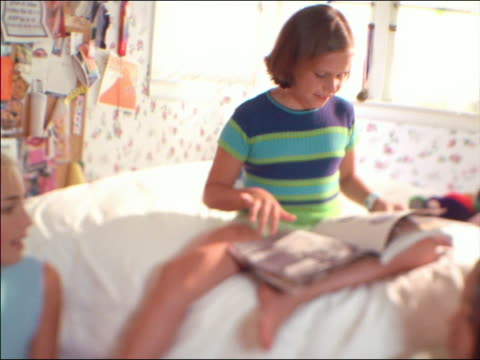 vidéos et rushes de low angle selective focus three girls in bedroom / girl on bed looks at magazine + other girl reaches to it - magazine