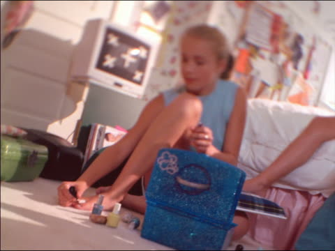 low angle pan selective focus three teen girls in bedroom looking at magazines, talking + painting nails - painting toenails stock videos & royalty-free footage