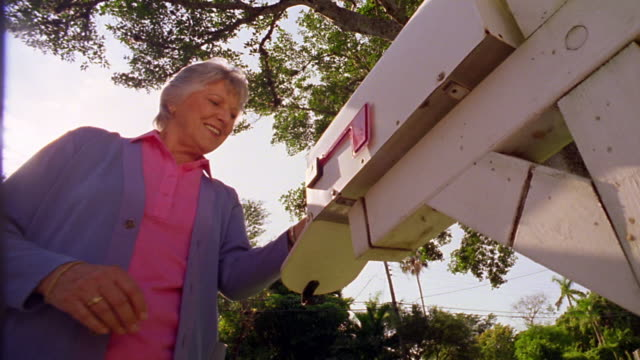 low angle ms senior woman getting mail out of mail box - mailbox stock videos and b-roll footage