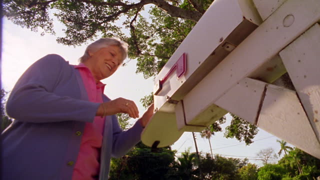 low angle ms senior woman getting mail out of mail box - message stock videos & royalty-free footage
