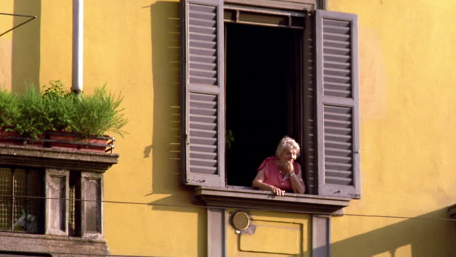 low angle senior woman looking out of shuttered window in yellow building / italy - loneliness stock videos & royalty-free footage