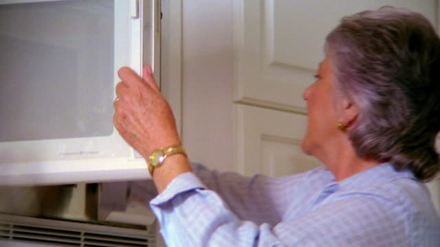 low angle pan senior woman putting food in microwave + heating - 電子レンジ点の映像素材/bロール