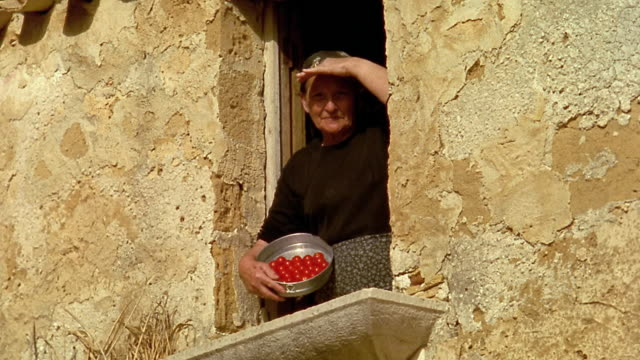 low angle ms senior woman shading eyes in window of house + holding bowl of tomatoes / custonaci, sicily - italian culture stock videos & royalty-free footage
