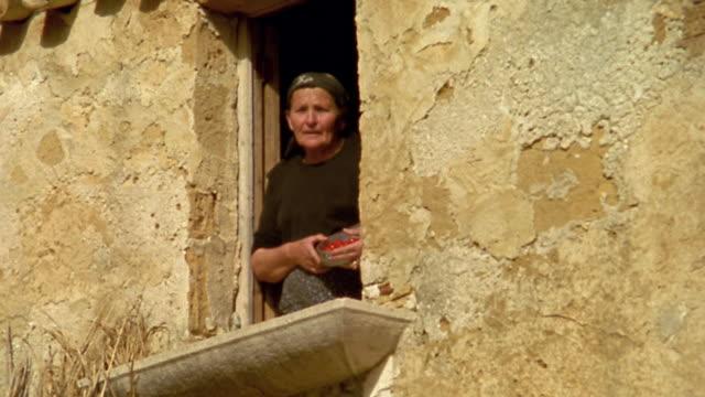 low angle ms senior woman talking in window of house / custonaci, sicily - italian culture stock videos & royalty-free footage