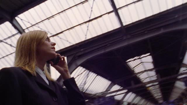 vídeos y material grabado en eventos de stock de low angle shaky businesswoman looking at train schedule + talking on cell phone / zurich train station - tabla de llegadas y salidas