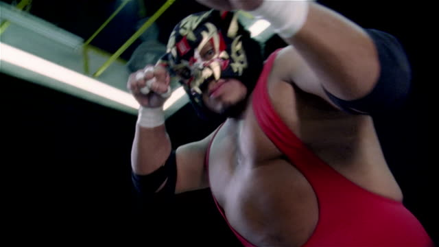 "vídeos de stock, filmes e b-roll de low angle shaky medium shot luchador ""black tiger"" looking at camera with arms in air/ pan kicking and punching toward camera/ monterrey, mexico - cultura mexicana"