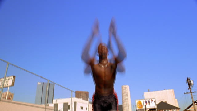 low angle shirtless black man doing straddle jump with outstretched arms touching his toes outdoors - doing the splits stock videos & royalty-free footage