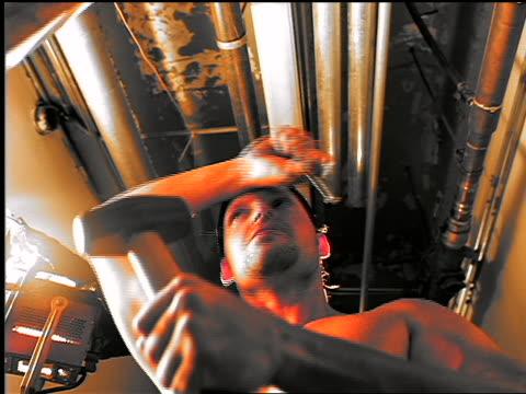 low angle shirtless man wearing bandanna hammering nail + wiping brow with arm - shirtless stock videos & royalty-free footage