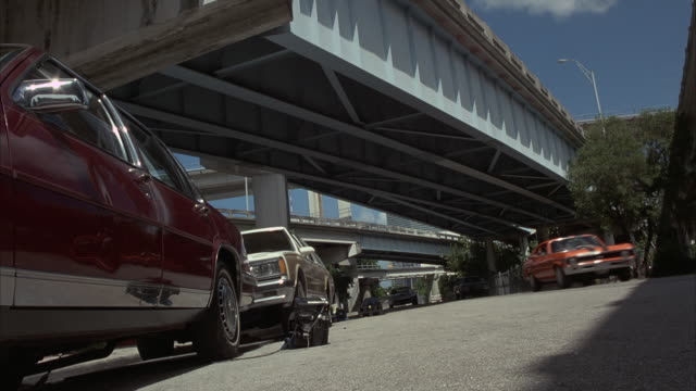 Low angle shot of a car crashing through parked cars.
