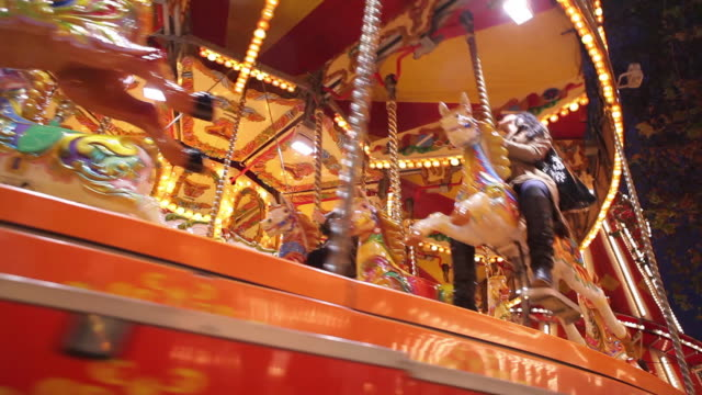 low angle shot of a carousel in motion at a funfair. - 回転遊具点の映像素材/bロール