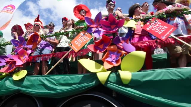 a low angle shot of a flowery parade float going past the camera in the brighton gay pride parade 2017 - festivalsflotte bildbanksvideor och videomaterial från bakom kulisserna