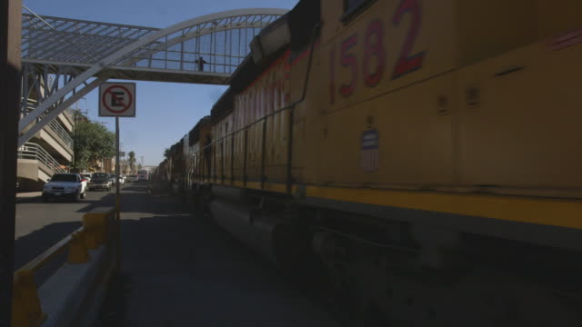 Low angle shot of a freight train moving through the Mexican town of Nogales.