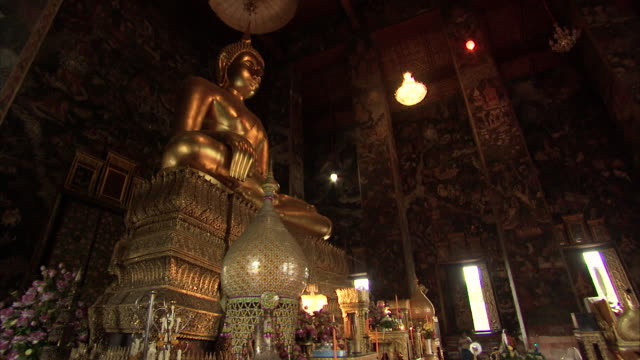 low angle shot of a golden buddha statue in a shrine in bangkok. - buddha stock-videos und b-roll-filmmaterial