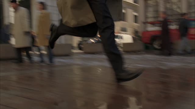 Low angle shot of a man in a trench coat running past pedestrians on a brick sidewalk.
