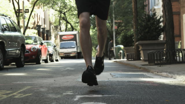 low angle shot of a man jogging along streets in manhattan. - human foot stock videos and b-roll footage