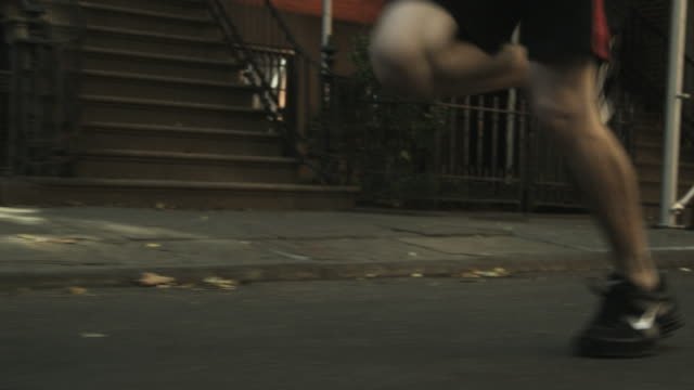 low angle shot of a man jogging along streets in manhattan. - human foot stock videos & royalty-free footage