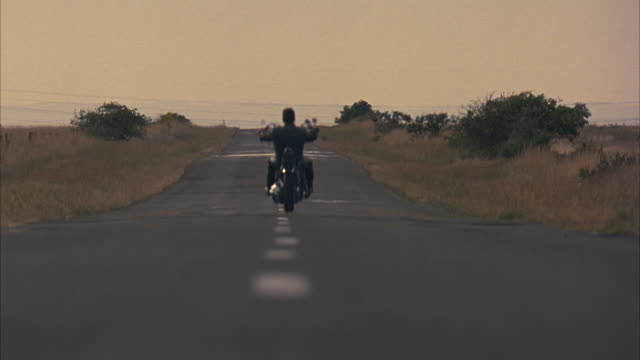 Low angle shot of a man riding a motorcycle down a deserted highway.