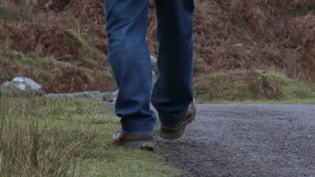 Low angle shot  of a man walking away on a rural Scottish road