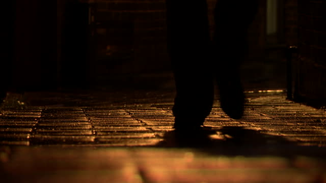 low angle shot of a man walking down an alley at night.  - kopfsteinpflaster stock-videos und b-roll-filmmaterial