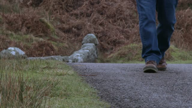 low angle shot  of a man walking toward the camera on a rural scottish road - approaching stock videos & royalty-free footage