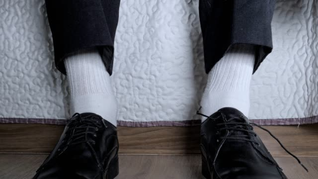 low angle shot of a man's hands tying up the ties of his elegant black dress shoes, businessman preparing for work / new york - pair stock videos & royalty-free footage