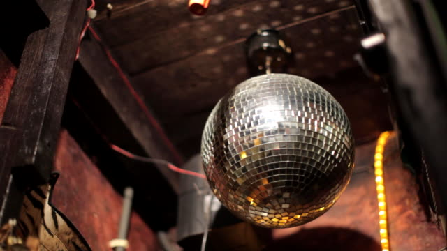 Low angle shot of a mirror ball slowly revolving.