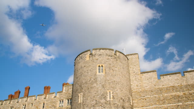 Low angle shot of a passenger aircraft flying over Windsor Castle.