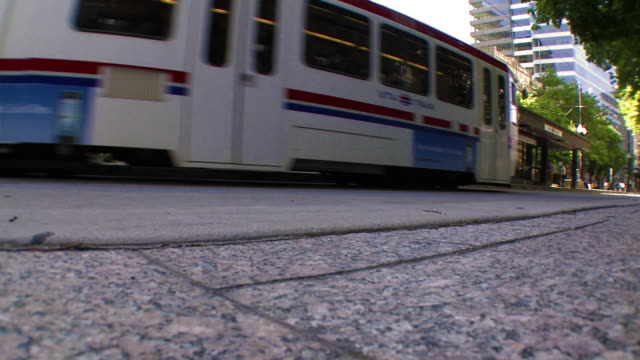 Low angle shot of a street as a tram and a car drive by.