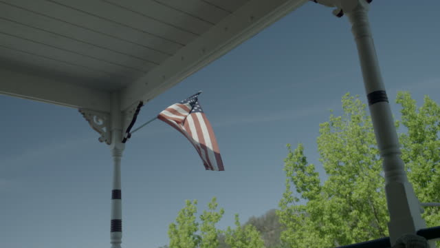low angle shot of a torn american flag gently swaying from a pole on a porch. - 破れている点の映像素材/bロール