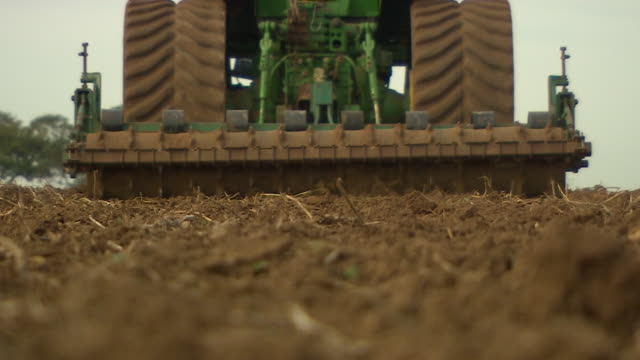 low angle shot of a tractor ploughing a field - trattore video stock e b–roll