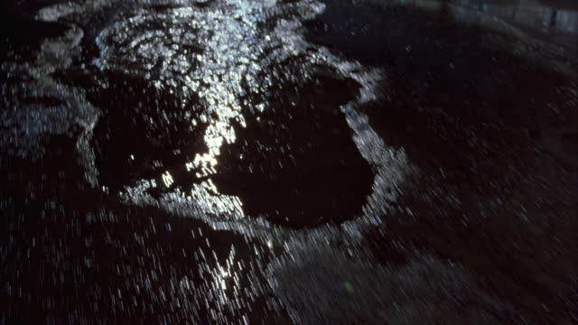 Low angle shot of a truck driving through puddles on the street.