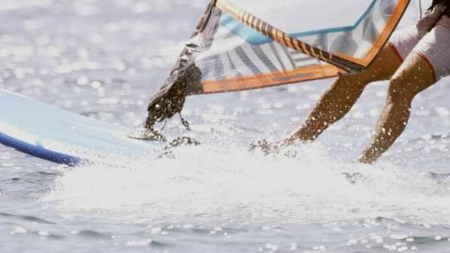 slo mo low angle shot of a windsurfer as he surfing on the ocean - water sport stock videos & royalty-free footage