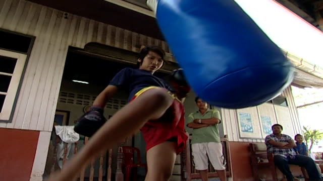 low angle shot of a young female thai boxer training in muay thai, as her trainer and father watch. muay thai, known as the art of eight limbs, is a... - human limb stock videos & royalty-free footage
