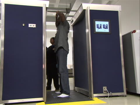 low angle shot of an african american male traveler entering a full body scan machine at airport security checkpoint and raising his arms above his... - man and machine stock videos & royalty-free footage