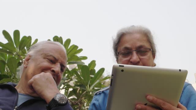 vídeos de stock e filmes b-roll de a low angle shot of an elder couple on a tablet - idoso na internet