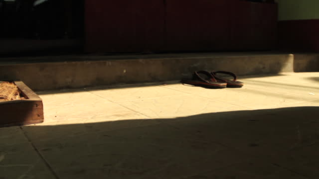 low angle shot of buddhist monks removing their shoes before entering a temple. - menschliche gliedmaßen stock-videos und b-roll-filmmaterial