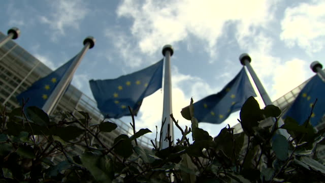 Low angle shot of EU flags outside EU Commission in Brussels