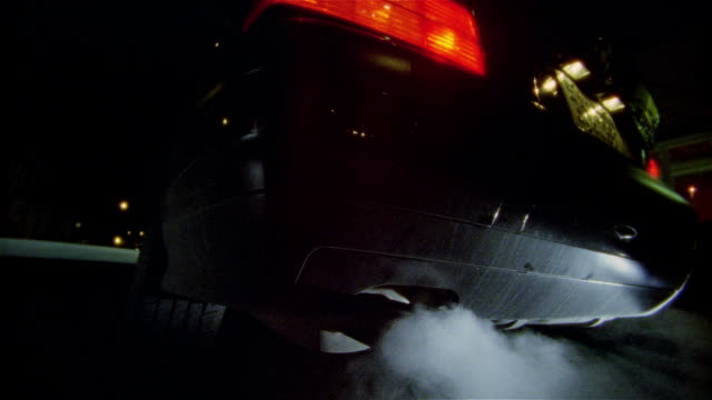 Low angle shot of exhaust spewing from tail pipes of car
