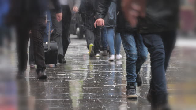 low angle shot of feet walking in the rain. - pioggia video stock e b–roll