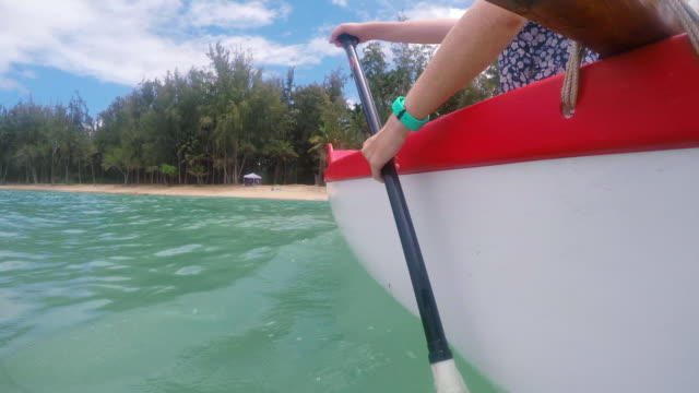low angle shot of girl paddling from the nose of outrigger canoe - oar stock videos and b-roll footage