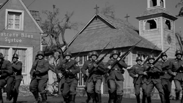 MS low angle Shot of group of Nazi soldiers charging toward shooting their weapons with church