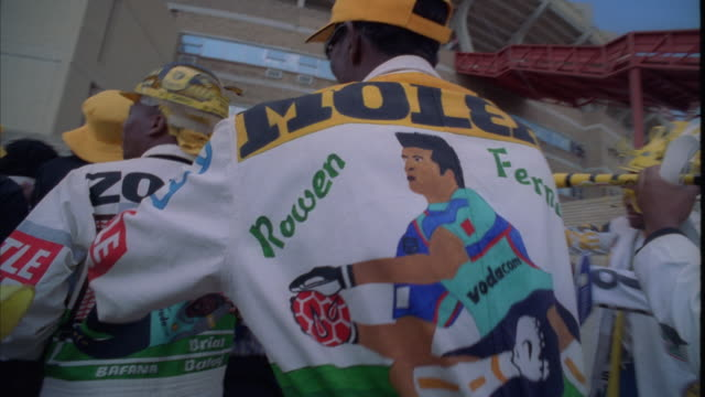 low angle shot of kaizer chiefs fans in painted overalls dancing outside a stadium - ソウェト点の映像素材/bロール