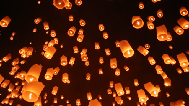 Low angle shot of lanterns floating in night sky