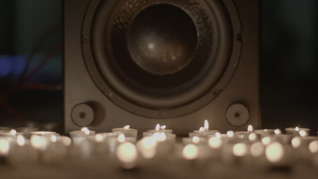 low angle shot of lit tea lights placed in front of a hi-fi speaker. - stereoanlage stock-videos und b-roll-filmmaterial