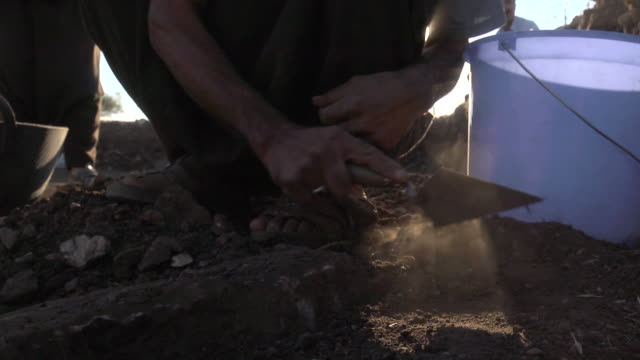 stockvideo's en b-roll-footage met low angle shot of men digging in the dirt at the gokeli tepe archaeology site, turkey. - emmer
